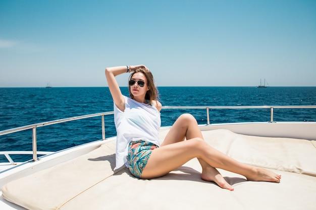青い海に浮かぶ豪華ヨットでリラックスした若い魅力的な女性を見る