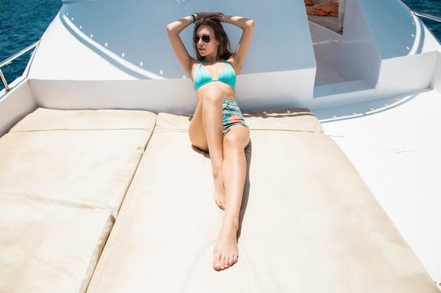 Вид на молодую привлекательную женщину, расслабляющуюся на роскошной яхте, плавающей в синем море