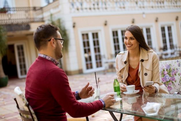 Вид на молодую пару, развлекающуюся, сидя вместе в городском кафе