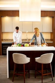 Вид на молодого человека, помогающего своей подруге готовить на современной кухне