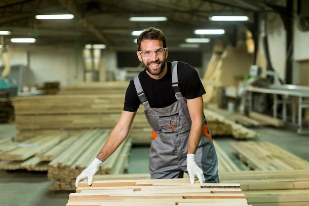 家具生産工場の若い労働者の作品を見る