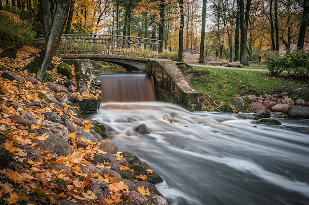 View of autumn river bank with small waterfall.