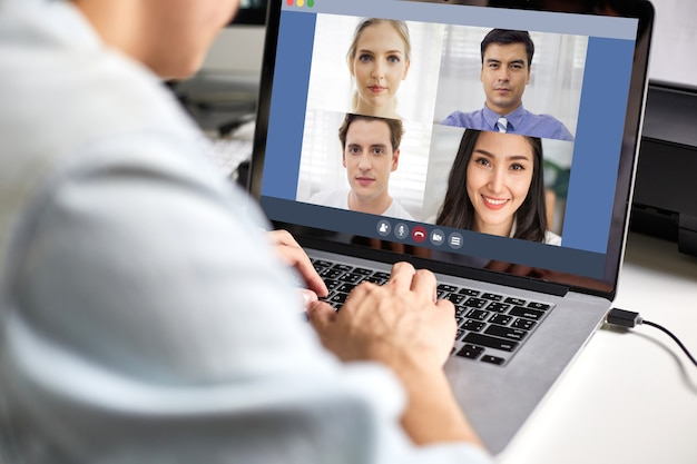 View of back man using laptop video conference and working with colleague