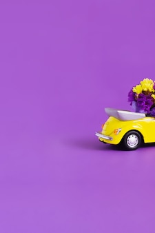 View of the back of the trunk of a bright yellow convertible car with a bouquet of flowers on a purple . concept holiday, delivery, art, , transport