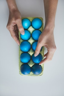 Above view background female hand arranging composition of painted blue easter eggs in crate on white, copy space