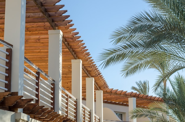 View to balcony of egypt resort hotel against blue sky and palm branch.