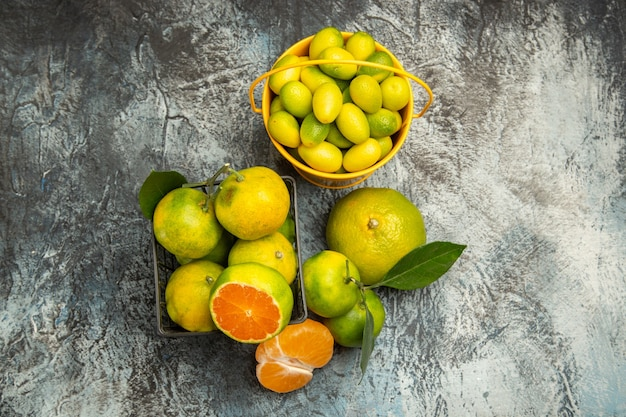 Sopra la vista di un cesto e di un secchio pieno di mandarini verdi freschi tagliati a metà e mandarino sbucciato su sfondo grigio