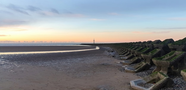 View of the beach in liverpool at sunset, rows of breakwaters, united kingdom