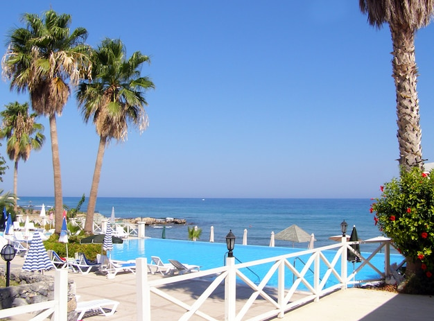 View of the beach on a sunny day on the mediterranean coast and a swimming pool with sun loungers
