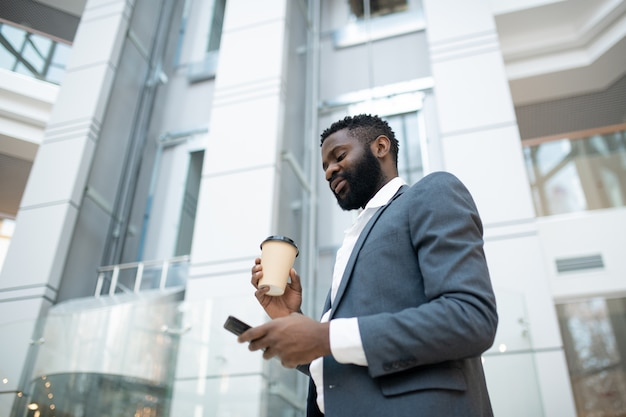 Below view of bearded black businessman in jacket answering in messenger and drinking coffee on move