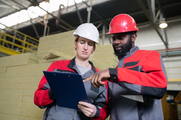 Below view of bearded black man in hardhat asking colleague about industrial plan while pointing at paper in clipboard