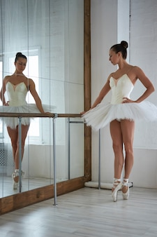 View of beautiful ballerina in tutu standing at barre with hand on hip and looking down. copyspace