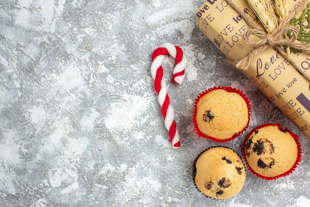 Above view of beautiful christmas packed gift with love inscription and small cupcakes on ice surface