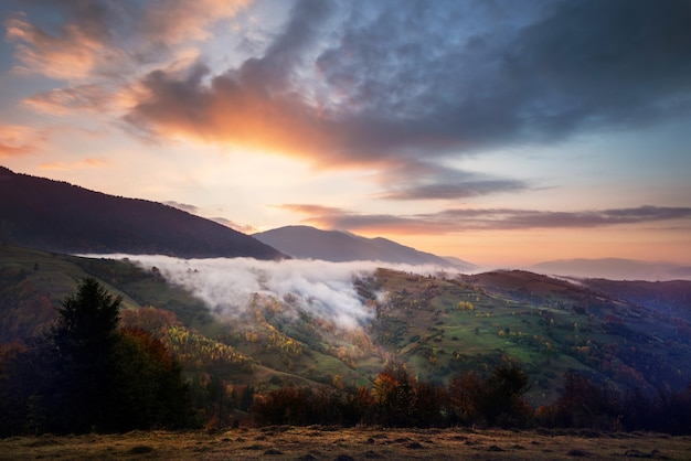 View of beautiful cloudy sky over hillside meadow. majestic landscape of mountains with smoke and dramatic bright sky on background. concept of nature and dawn.