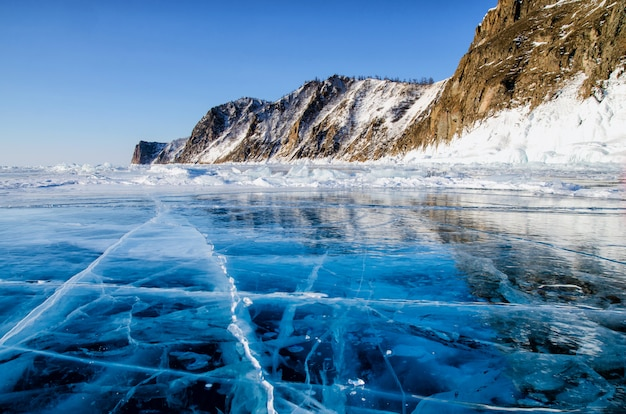 View of beautiful drawings on ice from cracks and bubbles of deep gas on surface of baikal lake in winter, russia
