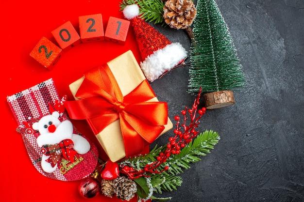 Sopra la vista di bellissimi accessori di decorazione regalo rami di abete numeri di calzino di natale su un tovagliolo rosso e cappello di babbo natale albero di natale su sfondo scuro