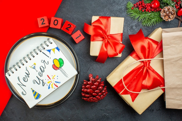 Above view of beautiful gifts and notebook with new year drawings on a plate conifer cone fir branches numbers on a dark table