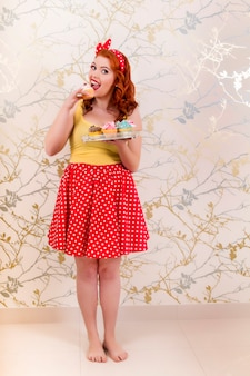View of a beautiful pinup redhead girl holding a tray of colorful cupcakes.