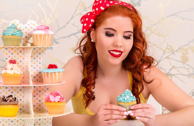 View of a beautiful pinup redhead girl with colorful cupcakes on a table.