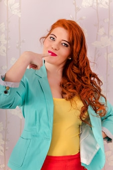 View of a beautiful redhead girl wearing colorful clothing.