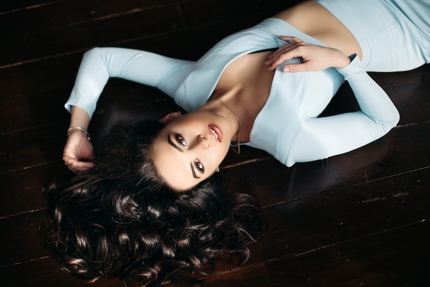 Above view of beautiful woman in blue dress lying on dark wooden floor.