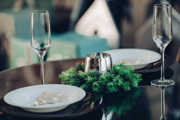 Vista sulla tavola rotonda splendidamente decorata con rami di abete naturale, candela, due flauti, piatti contro il divano classico in un appartamento moderno.