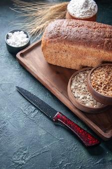 Sopra la vista di farina di fette di pane nero in una ciotola su tavola di legno e punte di coltello farina d'avena cruda di grano sul lato sinistro su sfondo invecchiato di colori misti