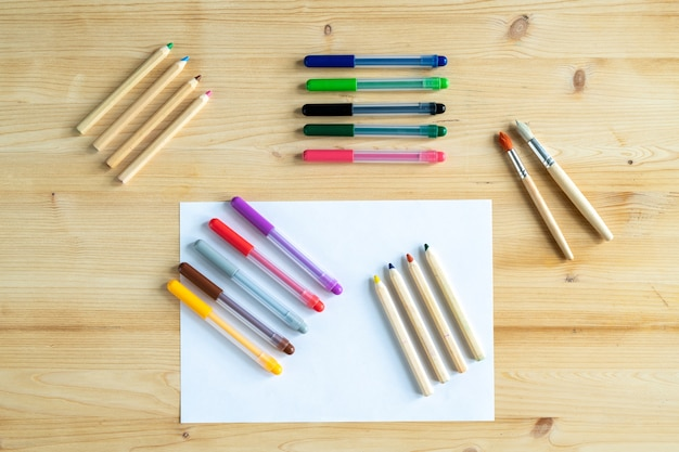 View of blank paper and several sets of crayons and pens and two paintbrushes on wooden table
