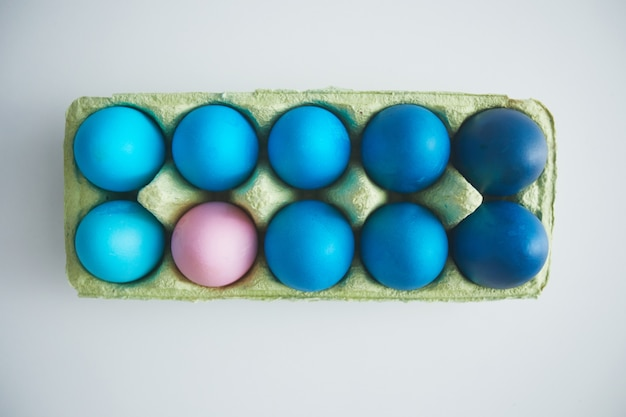 Above view of blue easter eggs in crate with pastel pink accent arranged in minimal composition on white background, copy space