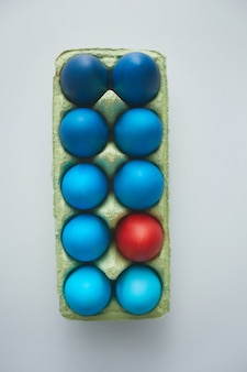 Above view of blue easter eggs in crate with red accent arranged in minimal composition on white background, copy space