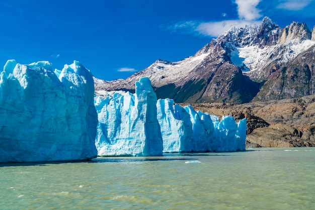 View of blue iceberg of grey glacier in grey lake and beautiful snowy mountain at torres del paine national park in southern chilean patagonia ice field.