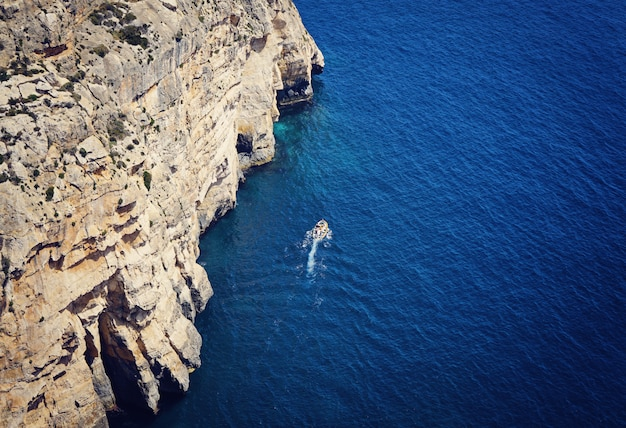 View of the blue sea and a small boat floating along the cliff