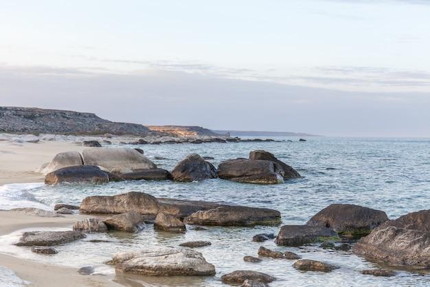 View of blue sea waves at rocky beach. horizon line. caspian sea, sandstone coast.