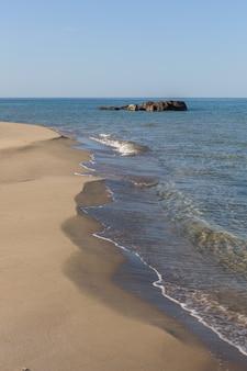 View of blue sea waves at sandy beach. horizon line. caspian sea, sandstone coast