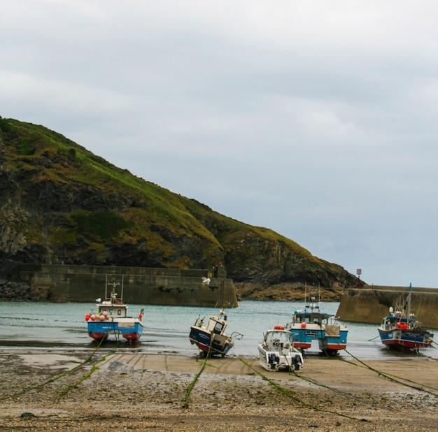 Vista delle barche su una spiaggia sabbiosa con una montagna e un cielo nuvoloso