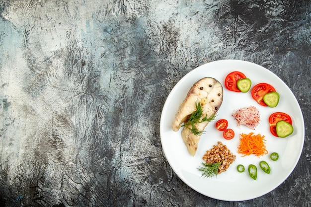 Above view of boiled fish buckwheat served with vegetables green on a white plate on ice surface with free space