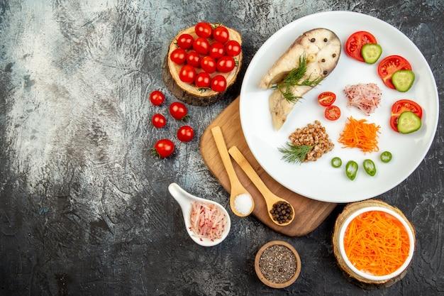 Sopra la vista del grano saraceno bollito del pesce servito con le verdure verdi su un piatto bianco sul tagliere di legno e delle spezie sulla superficie del ghiaccio