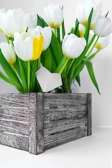 View of a bouquet of white tulips standing in a wooden box.