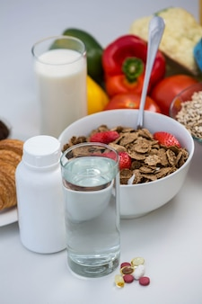 View of bowl of cereals, pills and food on a white table