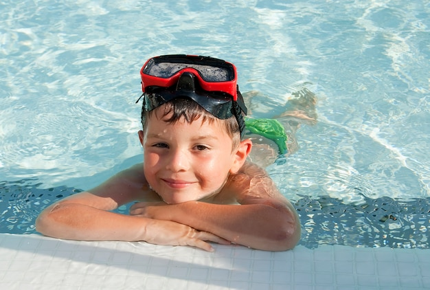 Above view of a boy into the swimming pool while looking to camera