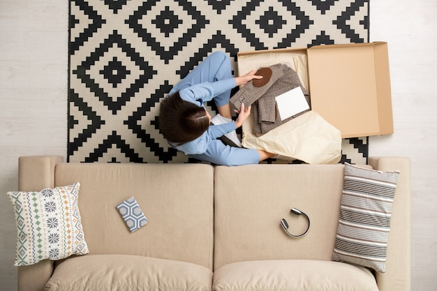View of brunette girl in blue pajamas sitting by couch in living-room and looking at new folded checkered jacket in box from online shop