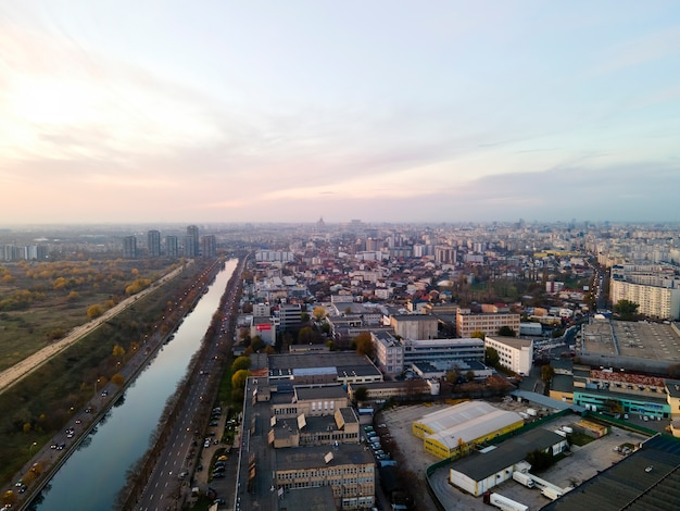 View of bucharest from the drone, water channel, park with greenery and lakes, multiple residential and commercial buildings, sunset, romania