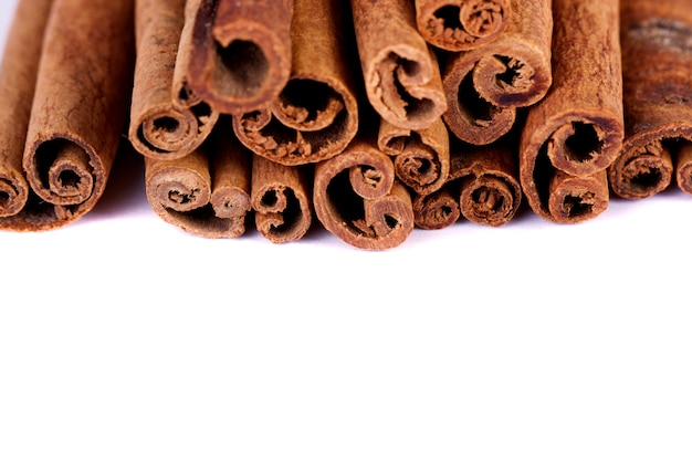View of a bunch of cinnamon spice quills isolated on a white background.