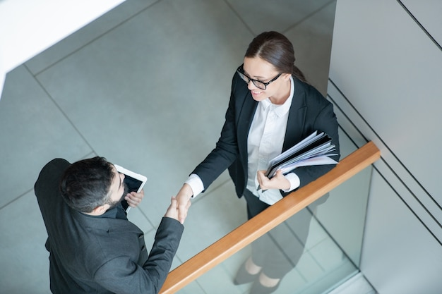 Above view of businessman with tablet handshaking with female analyst after negotiations