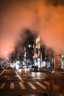 View of busy night road in smoke