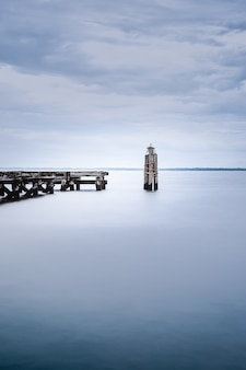 View of a calm sea near a wooden dock on a gloomy day
