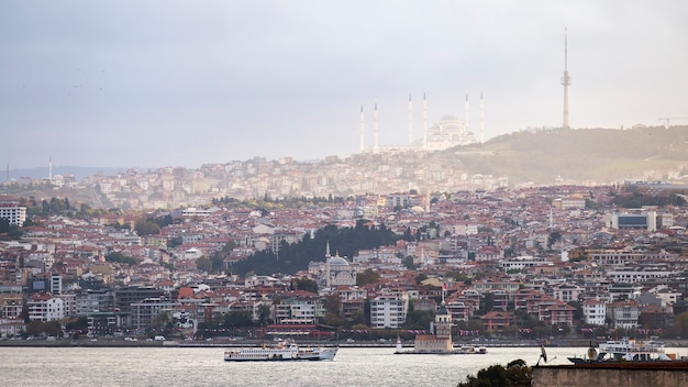 View of camlica mosque located on a hill with residential buildings, bosphorus strait, floating ship and leander's tower, istanbul, turkey