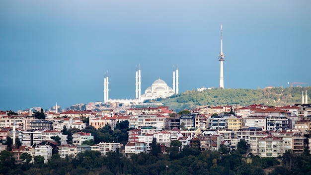 View of camlica mosque located on a hill with residential buildings on the foreground, tower on the top of the hill, cloudy weather, istanbul, turkey