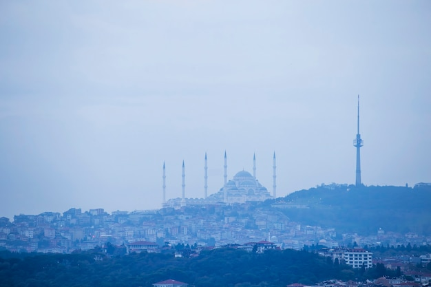 View of camlica mosque located on a hill with residential buildings on the slope, tower on the top of the hill, cloudy weather, istanbul, turkey