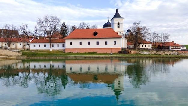 Veduta del monastero di capriana. la chiesa di pietra, gli edifici, gli alberi spogli. un lago in primo piano, bel tempo in moldova